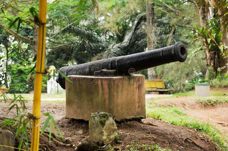 Die alte schwarze Eisenkanone, die auf dem Block des weißen Steins benutzt für Verteidigungsrückseite in der Geschichte stillsteh stockbilder