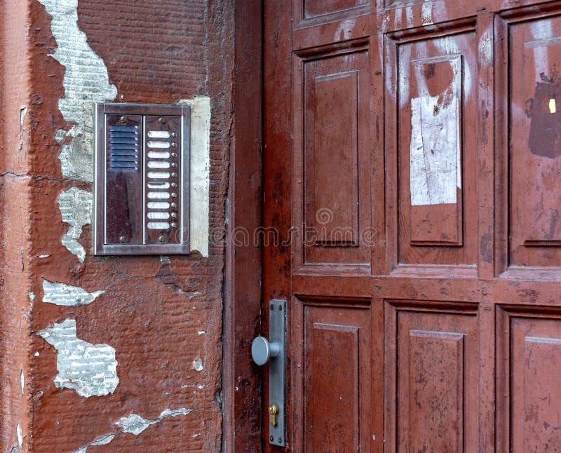 Die alte Tür des Hauses Wechselsprechanlage auf der alten Wand lizenzfreie stockbilder