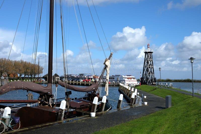 Die alte traditionelle Yacht und der moderne Schwarzweiss-Leuchtturm lizenzfreie stockfotografie