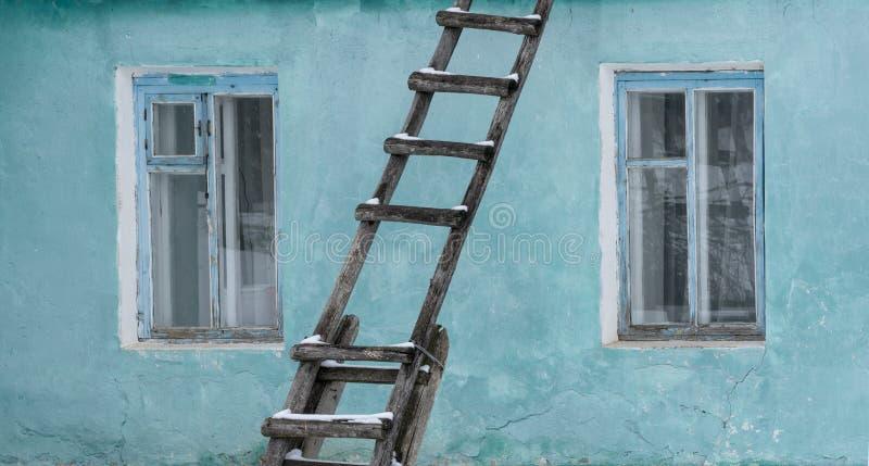 Die alte Wand des Hauses wird in einer hellen Türkisfarbe mit zwei Windows gemalt, zwischen denen es ein altes hölzernes Treppenh lizenzfreie stockfotografie