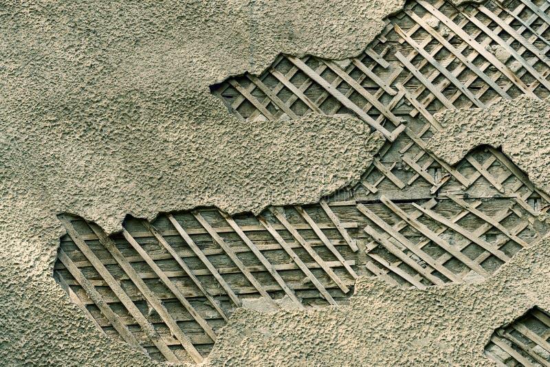 Die alte Wand mit eingestürztem Gips und sichtbaren hölzernen Kisten stockfoto