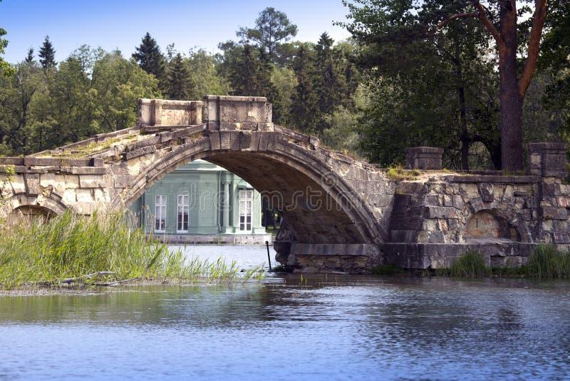 Die alte zerstörte Brücke im Park und im Pavillon von Venus (1793) ist unter einem Brückenbogen sichtbar Gatchina, St Petersburg, stockbild