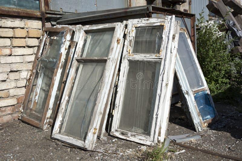 Die alten Fenster in einem Holzrahmen mit schäbiger weißer Farbe und in defekter Glaslüge in einem Haufen im Dump lizenzfreies stockfoto