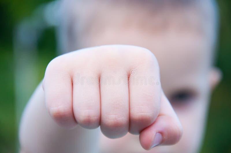 Die angehobene Hand des kleinen Jungen preßte in eine Faust auf der Straße zusammen stockfotos