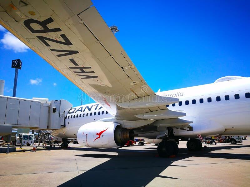 Die Ansicht unter den flachen linken Flügel Fluglinie Qantass des inländischen Flugzeugbaumusters: Boeing 737 auf der Rollbahn lizenzfreie stockbilder