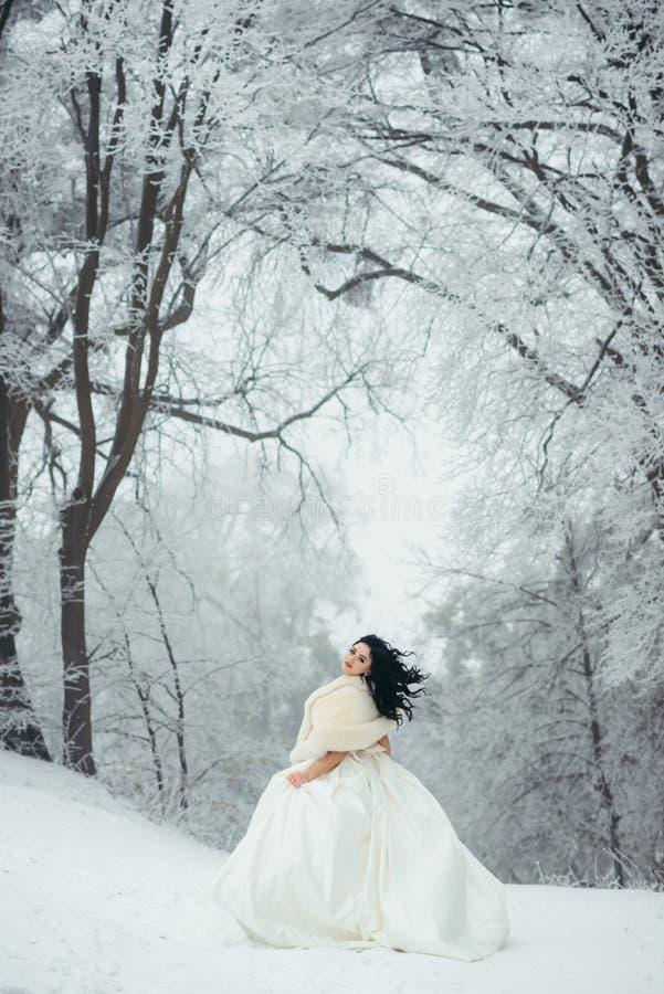 Die Ansicht in voller Länge der reizend Braut mit dem langen schönen schwarzen Haar, das auf dem schneebedeckten Weg im Wald steh lizenzfreies stockbild