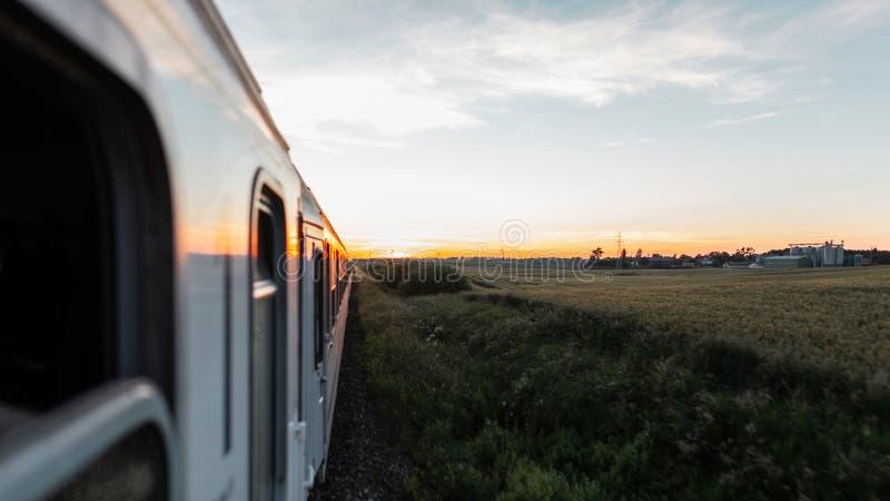 Die Ansicht vom Zugfenster, das die Lastwagen auf dem Feld und dem orange Sommersonnenuntergang übersieht lizenzfreie stockfotografie