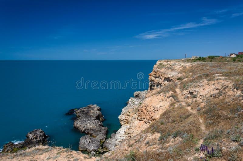 Die Ansicht von der Höhe über dem Meer felsiges Ufer und Boote im Meer am sonnigen Tag Feld des grünen Grases gegen einen blauen  lizenzfreie stockbilder