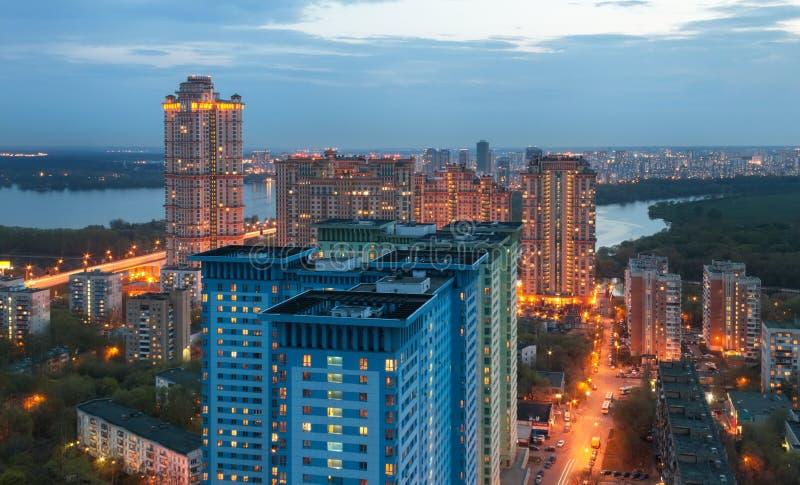 Die Ansicht von der Höhe auf hohem Gebäude auf den Stadtränden von Moskau, in der Dämmerung auf dem Hintergrund des Flusses lizenzfreies stockfoto