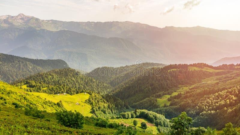 Die Ansicht von der Höhe eines grünen Gebirgstales mit den Wohngebäuden umgeben durch das Hochgebirge, belichtet durch lizenzfreies stockfoto