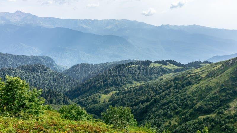Die Ansicht von der Höhe eines grünen Gebirgstales mit den Wohngebäuden umgeben durch Hochgebirge Snow-capped Berg stockfotos