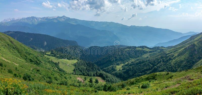 Die Ansicht von der Höhe eines grünen Gebirgstales mit den Wohngebäuden umgeben durch Hochgebirge Snow-capped Berg lizenzfreies stockbild