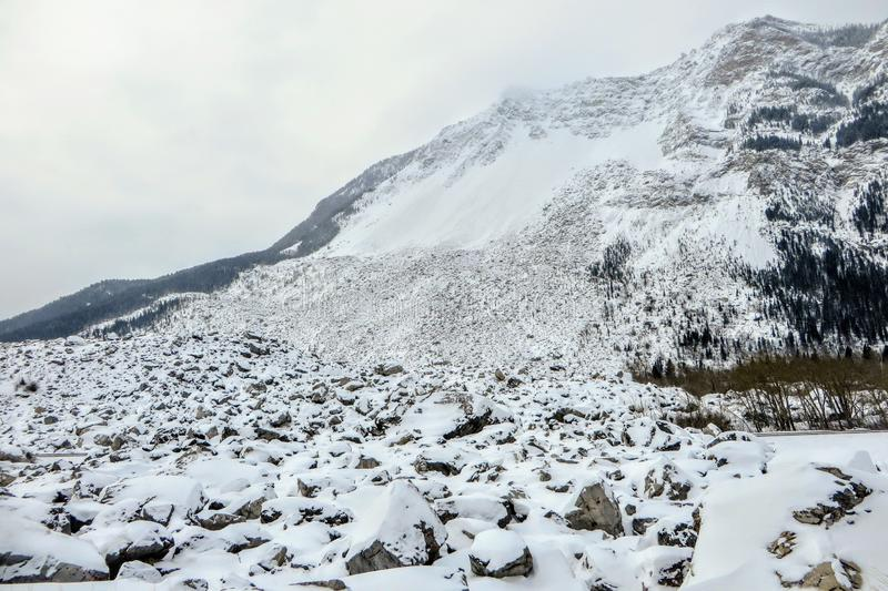 Die Ansicht von einer Basis eines Berges, in dem ein enormer Bergsturz stattfand Enorme Flusssteine zeichnen den Berg, der im Sch lizenzfreie stockfotografie