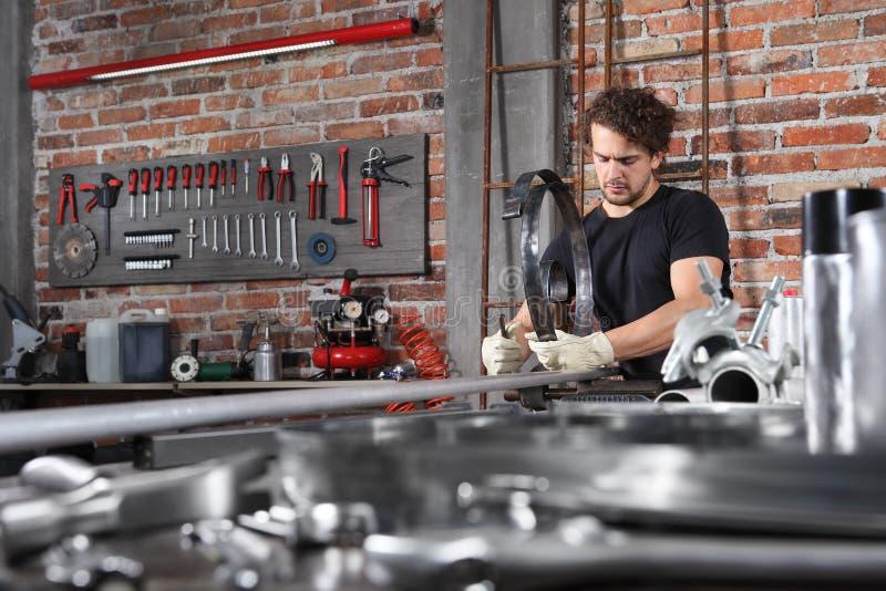Die Arbeit der Werkstatt in der Heimwerkerwerkstatt mit dem Griff der Bank fixiert ein Metall auf der Werkbank voller Wrenches, G lizenzfreie stockfotografie