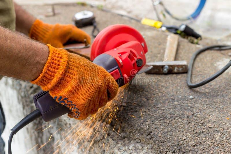 Die Arbeitskraft benutzt einen Winkel-Antriebsschleifer, um mit einer Metallecke zu arbeiten Winkel-Antriebsschleifer in der Akti stockbilder