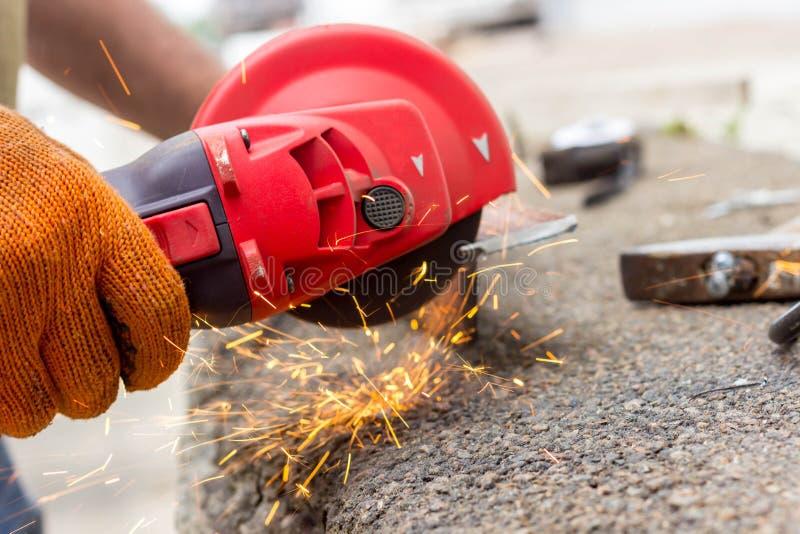 Die Arbeitskraft benutzt einen Winkel-Antriebsschleifer, um mit einer Metallecke zu arbeiten Winkel-Antriebsschleifer in der Akti lizenzfreies stockbild