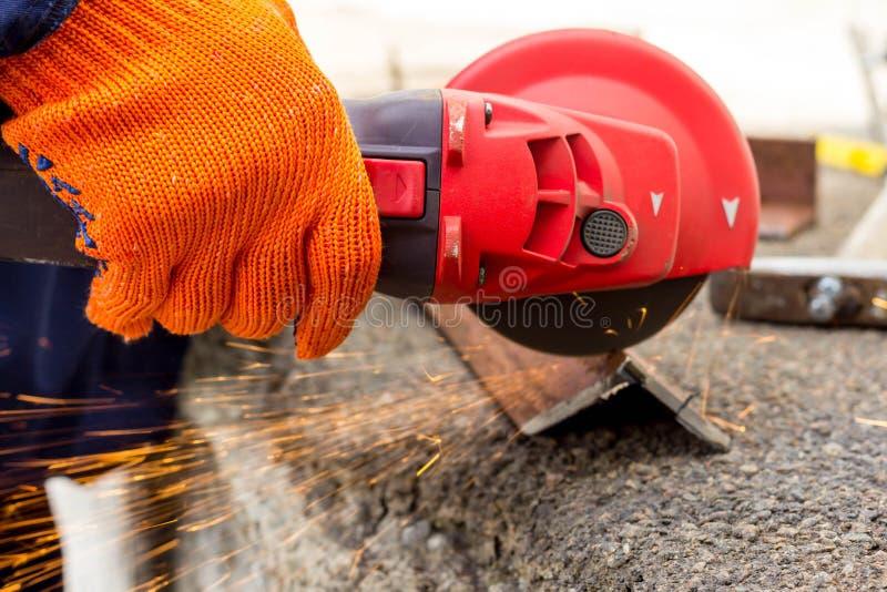 Die Arbeitskraft benutzt einen Winkel-Antriebsschleifer, um mit einer Metallecke zu arbeiten Winkel-Antriebsschleifer in der Akti stockfoto
