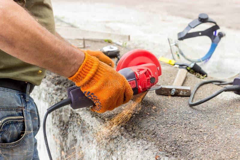 Die Arbeitskraft benutzt einen Winkel-Antriebsschleifer, um mit einer Metallecke zu arbeiten Winkel-Antriebsschleifer in der Akti lizenzfreie stockfotos