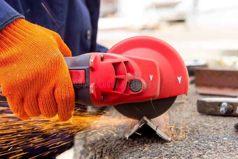 Die Arbeitskraft benutzt einen Winkel-Antriebsschleifer, um mit einer Metallecke zu arbeiten Winkel-Antriebsschleifer in der Akti stockfotografie