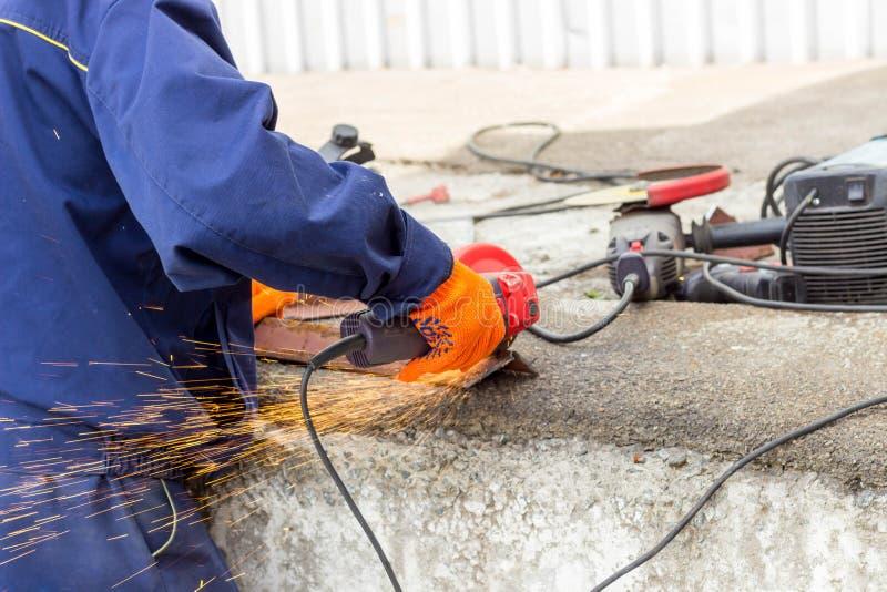 Die Arbeitskraft benutzt einen Winkel-Antriebsschleifer, um mit einer Metallecke zu arbeiten Winkel-Antriebsschleifer in der Akti stockbild
