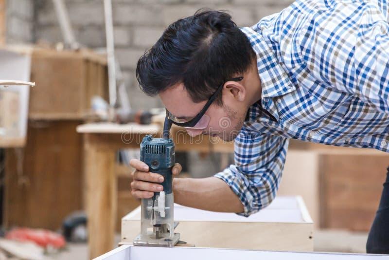 Die Arbeitskraft, die den Rand des hölzernen Brettes Gitterwerk verwendend schneidet, sah lizenzfreies stockfoto