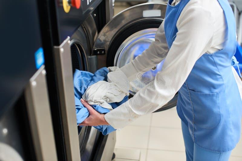 Die Arbeitskraft lädt die Wäschereikleidung in die Waschmaschine stockbild