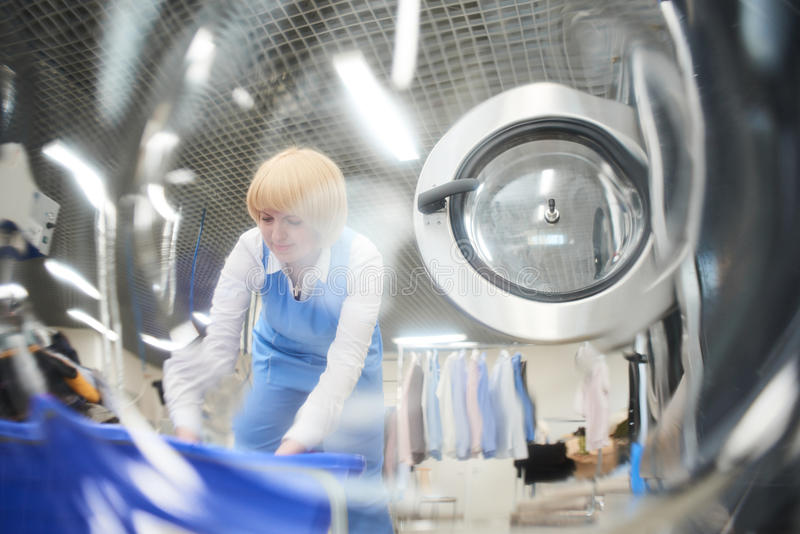 Die Arbeitskraft lädt die Wäschereikleidung in die Waschmaschine lizenzfreies stockbild
