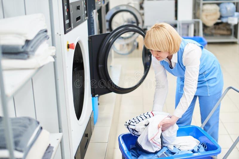 Die Arbeitskraft lädt die Wäschereikleidung in die Waschmaschine stockfotografie