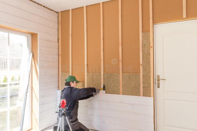 Die Arbeitskraft macht Vollendenarbeiten von den Wänden mit einem weißen hölzernen Brett, unter Verwendung des Laserstrahlniveaus lizenzfreie stockfotografie