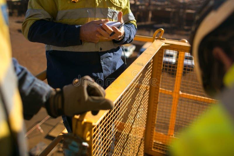 Die Arbeitskraft, die PersonalRisikobeurteilung betrachtet, nehmen Buch f?nf am Bau lizenzfreies stockbild