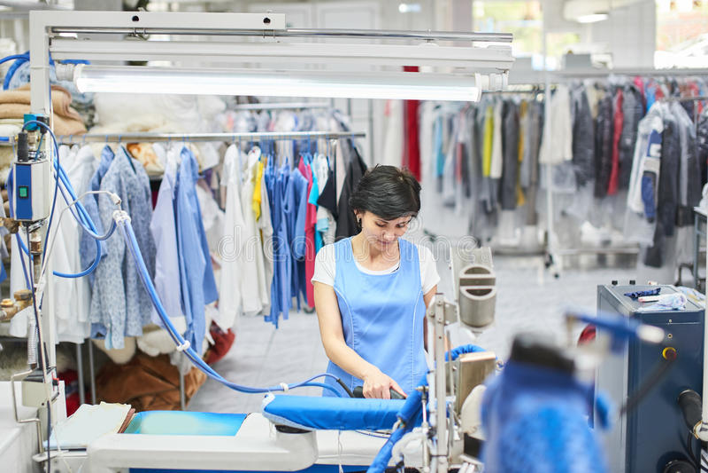 Die Arbeitskraft-Wäscherei, die gebügelt wird, kleidet das trockene Eisen lizenzfreie stockbilder