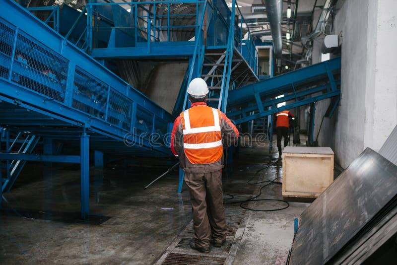 Die Arbeitskraft wäscht die Ausrüstung in der Abfallsortieranlage Überschüssige Verarbeitungsanlage Technologischer Prozess Wiede stockfotografie
