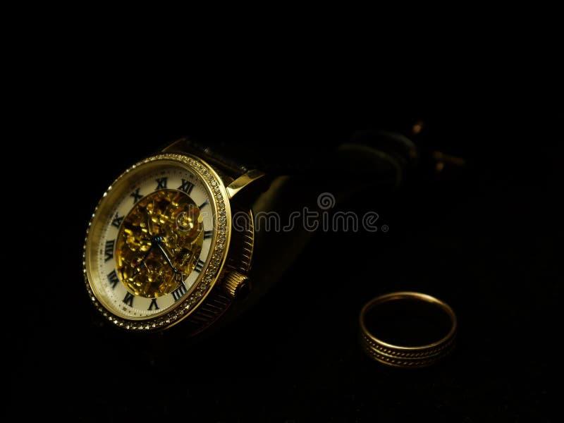 Die Armbanduhr und ein Ring der Männer auf einem schwarzen Samt lizenzfreie stockfotos
