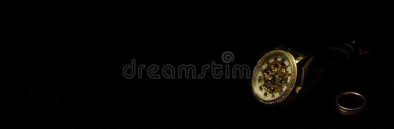 Die Armbanduhren und ein Ring der Männer auf einem schwarzen Samt stockbild
