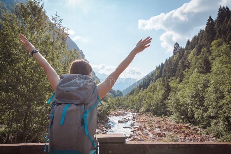 Die Arme der Frau hoben auf eine Brücke an, die einen Fluss kreuzt, der durch Berge umgeben wurde stockbilder