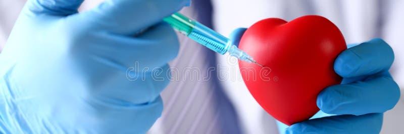 Die Arztarme, die schützende blaue Handschuhe tragen, haften Nadel in Herz lizenzfreie stockbilder
