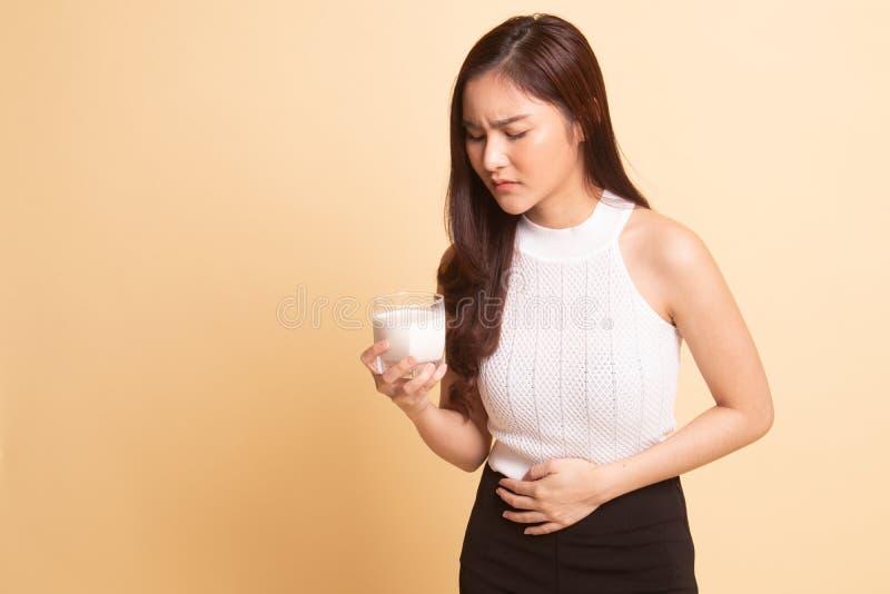 Die Asiatin, die ein Glas Milch trinkt, erhielt Magenschmerzen auf beige Hintergrund lizenzfreie stockfotos