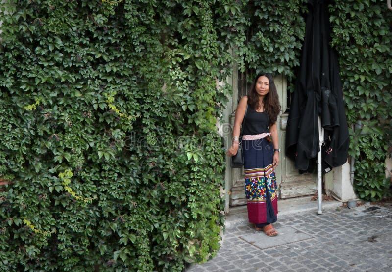 Die Asiatin, die vor Efeu steht, bedeckte Wand lizenzfreie stockbilder