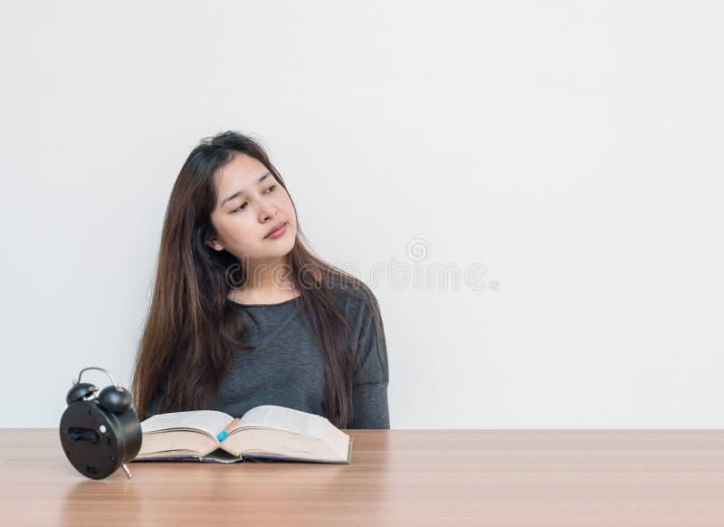 Die asiatische Frau der Nahaufnahme, die für sitzt, las ein Buch mit denkendem Gesichtsgefühl und betrachtet den Leerraum des Bil stockfoto