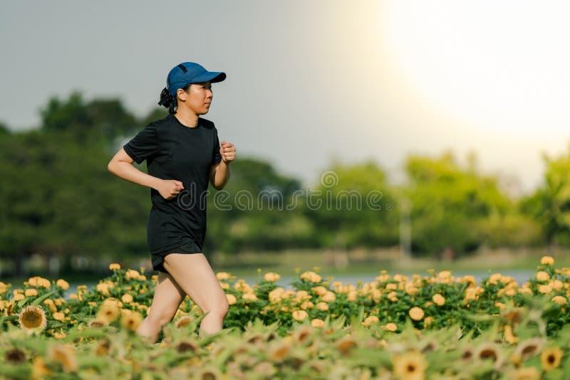 Die asiatische Frau von mittlerem Alter, die ein schwarzes Kleid, den blauen Hut, laufend in den Park trägt, erhalten das Sonnenl stockbilder