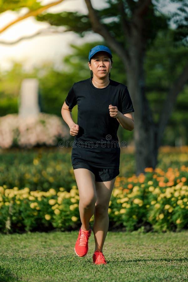 Die asiatische Frau von mittlerem Alter, die ein schwarzes Kleid, den blauen Hut, laufend in den Park tr?gt, erhalten das Sonnenl lizenzfreie stockbilder