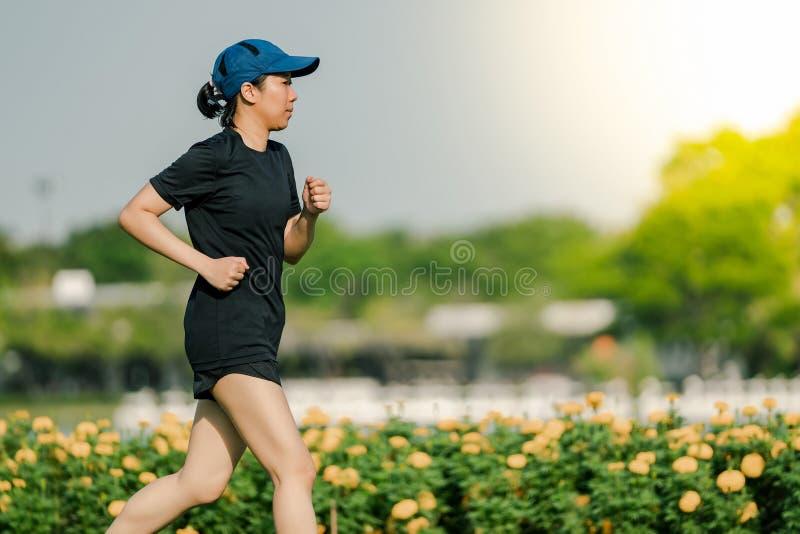 Die asiatische Frau von mittlerem Alter, die ein schwarzes Kleid, den blauen Hut, laufend in den Park tr?gt, erhalten das Sonnenl stockfotos