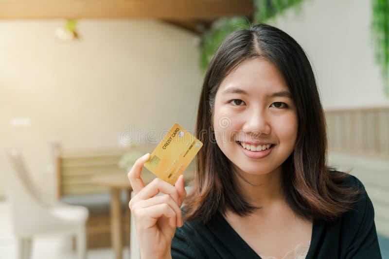 Die asiatische Schönheit der Nahaufnahme, die ein schwarzes Hemd sitzt im Haus trägt, haben ein glückliches Gesicht der Kreditkar stockbild