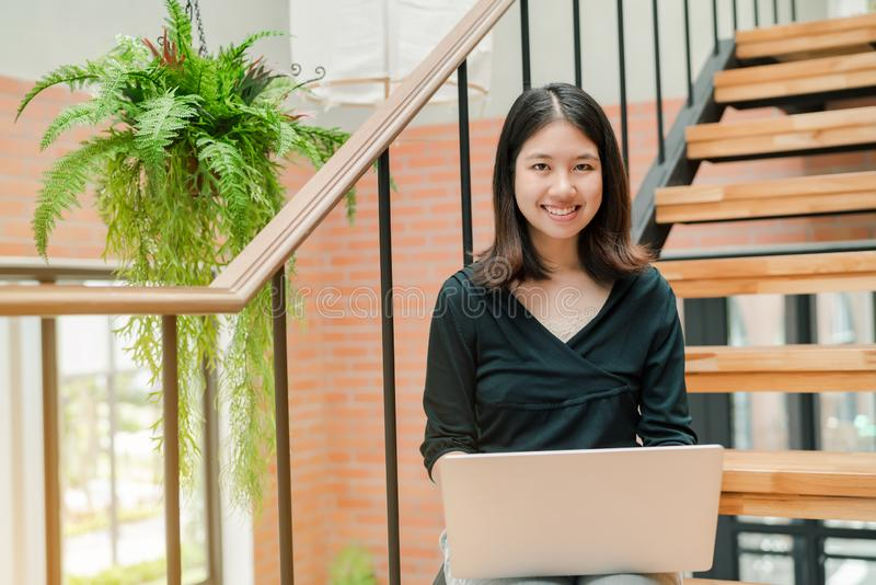 Die asiatische Schönheit der Nahaufnahme, die ein schwarzes Hemd sitzt in der Treppe im Haus trägt, benutzen eine Laptop-Computer lizenzfreies stockfoto