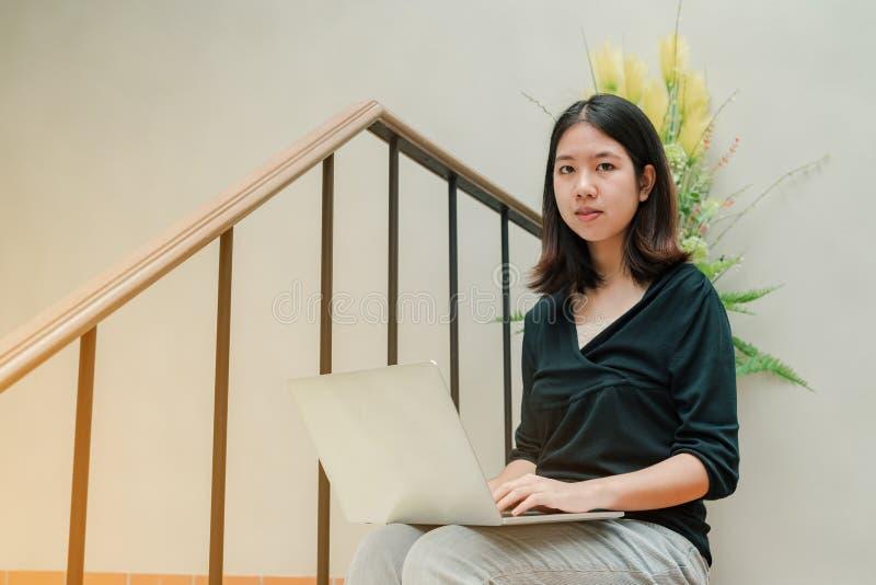 Die asiatische Schönheit der Nahaufnahme, die ein schwarzes Hemd sitzt in der Treppe im Haus trägt, benutzen eine Laptop-Computer lizenzfreie stockfotos