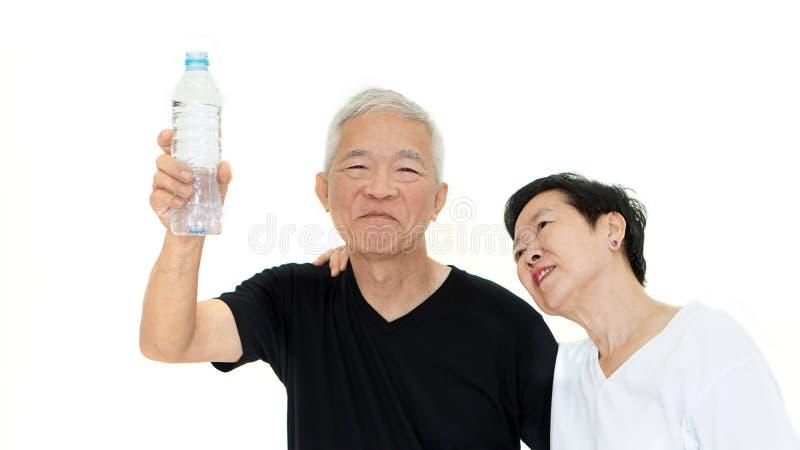 Die asiatischen älteren Paare, die Wasserflasche halten, bleiben Hydrat für Gesundheit stockfotos