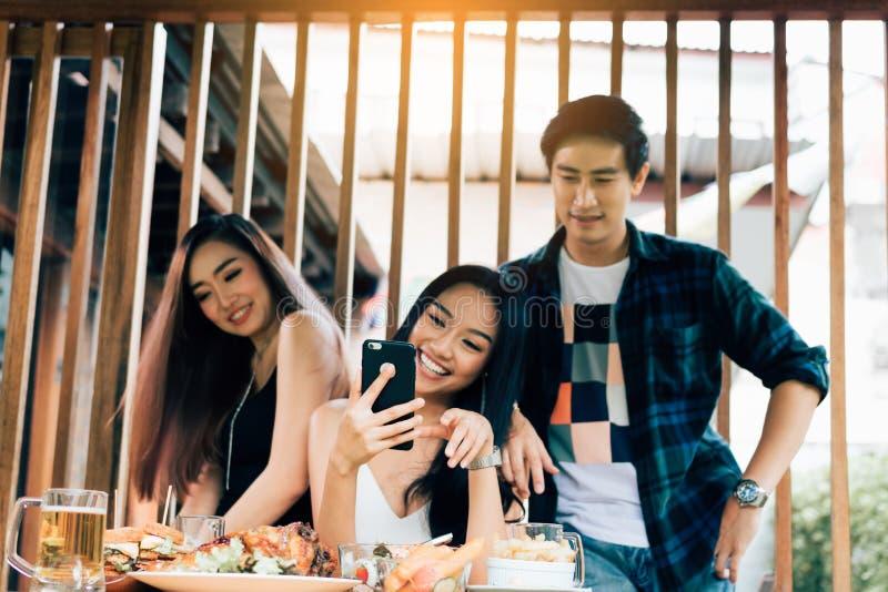 Die asiatischen Gruppenleute, die am Restaurant sich treffen mit, genießen, zusammen zu lachen lizenzfreie stockfotografie