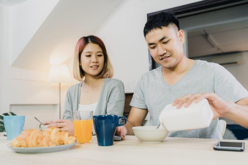 Die asiatischen Paare, die, Getreide in der Milch, Brot frühstücken und Orangensaft nach trinken, wachen morgens auf lizenzfreie stockfotos