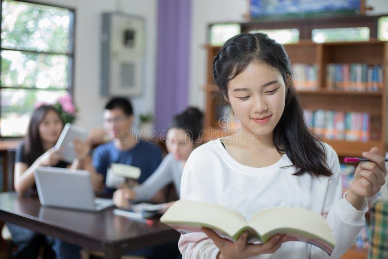 Die asiatischen Studentinnen, die für Auswahl halten, buchen in der Bibliothek stockfotografie