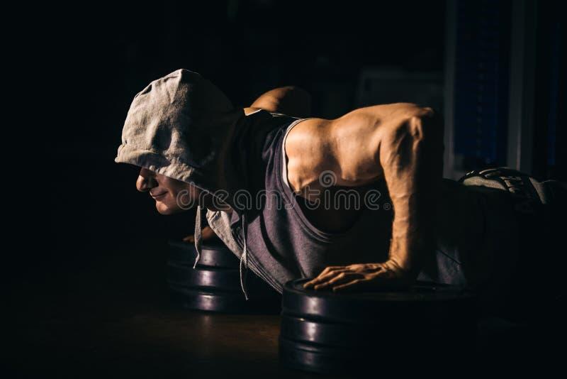 Die Athletenstöße, Pressungen vom Boden Schwarzer Hintergrund stockbild